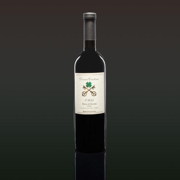 «U Suli» Nero d'Avola D.O.C. Reflets rouges pourpres profonds; parfum de figues, cerises et vanille. Large en bouche. C'est un bon vin de repas. Rarement réperible dans la version D.O.C., nous voulions créer un allrounder avec pedigree. Persistant dans l'arrière-goût et sans complications. Idéal pour ceux qui recherchent des goûts simples et originaires. Écouter la déscription